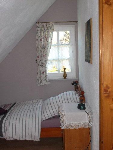 kleines Schlafzimmer; rechts die Tür zum Bad